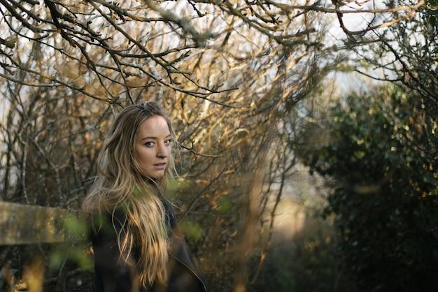 Jovem loira com um casaco preto em pé no caminho cercado por árvores sem folhas