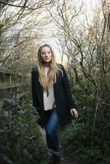 Jovem loira com um casaco preto parada em um caminho cercado por árvores sem folhas