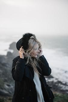 Jovem loira com um chapéu, caminhando em uma costa rochosa em um clima ventoso