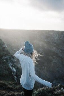 Jovem loira com um chapéu, caminhando na praia em um tempo ventoso