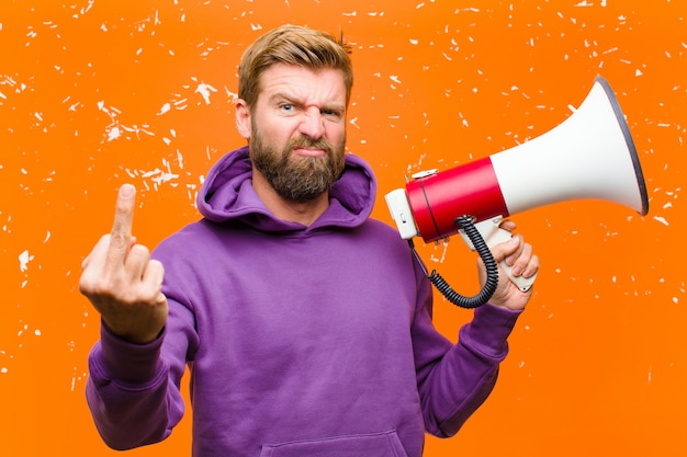 Jovem loira com um megafone, vestindo um capuz roxo contra parede laranja danificada