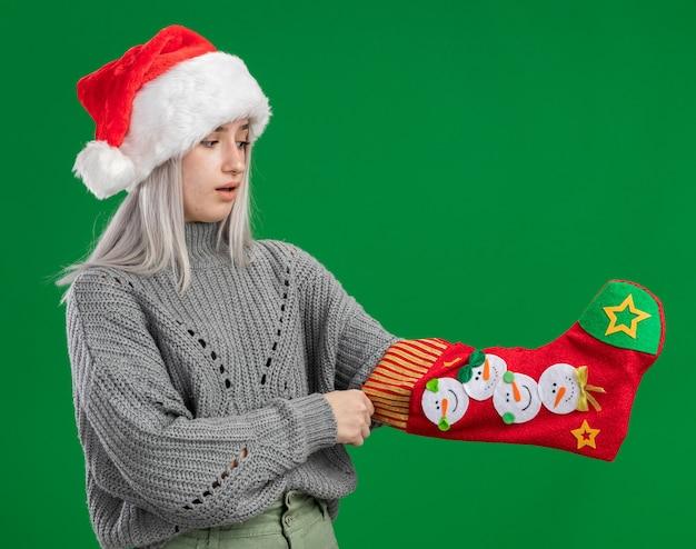 Jovem loira com um suéter de inverno e um chapéu de papai noel com uma meia de natal na mão olhando para ela surpresa de pé sobre um fundo verde