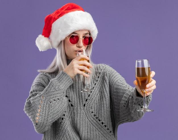 Jovem loira com um suéter de inverno e um chapéu de papai noel segurando duas taças de champanhe, bebendo, parecendo confiante e confiante em pé sobre a parede roxa