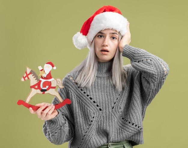 Jovem loira com um suéter de inverno e um chapéu de papai noel segurando um brinquedo de natal confuso com a mão na cabeça em pé sobre uma parede verde