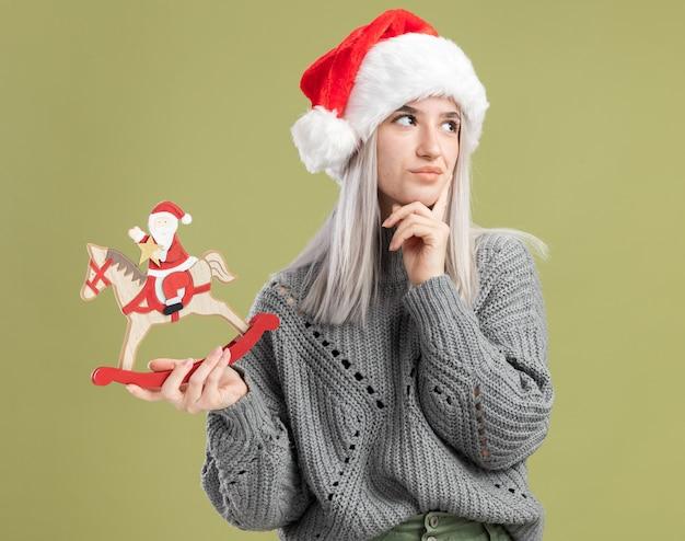 Jovem loira com um suéter de inverno e um chapéu de papai noel segurando um brinquedo de natal olhando de lado perplexa em pé sobre a parede verde