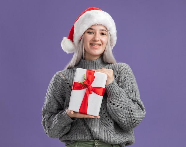 Jovem loira com um suéter de inverno e um chapéu de papai noel segurando um presente com um sorriso no rosto feliz em pé sobre a parede roxa