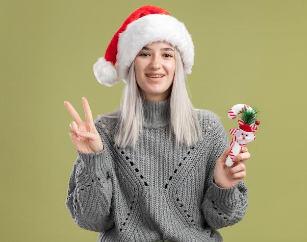 Jovem loira com um suéter de inverno e um chapéu de papai noel segurando uma bengala de doces de natal e sorrindo alegremente mostrando o sinal v em pé sobre a parede verde