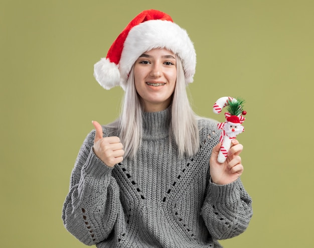Jovem loira com um suéter de inverno e um chapéu de papai noel segurando uma bengala de doces de natal e sorrindo alegremente mostrando os polegares para cima em pé sobre a parede verde