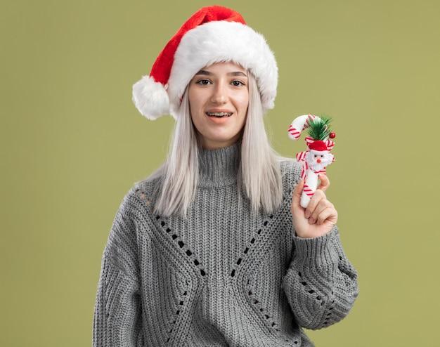 Jovem loira com um suéter de inverno e um chapéu de papai noel segurando uma bengala de doces de natal, feliz e animada em pé sobre a parede verde