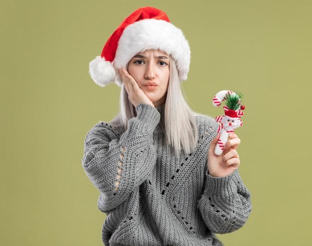 Jovem loira com um suéter de inverno e um chapéu de papai noel segurando uma bengala de doces de natal, sendo confusa em pé sobre a parede verde