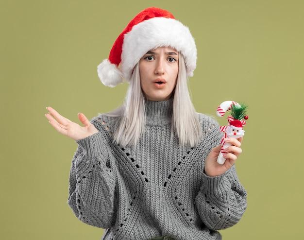 Jovem loira com um suéter de inverno e um chapéu de papai noel segurando uma bengala de doces de natal surpresa em pé sobre a parede verde