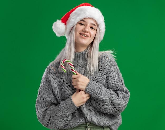 Jovem loira com um suéter de inverno e um chapéu de papai noel segurando uma bengala de doces, olhando para a câmera, feliz e positiva, sorrindo em pé sobre fundo verde
