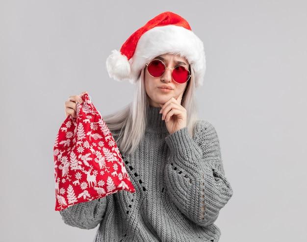 Jovem loira com um suéter de inverno e um chapéu de papai noel segurando uma bolsa vermelha de papai noel com presentes de natal, parecendo confusa