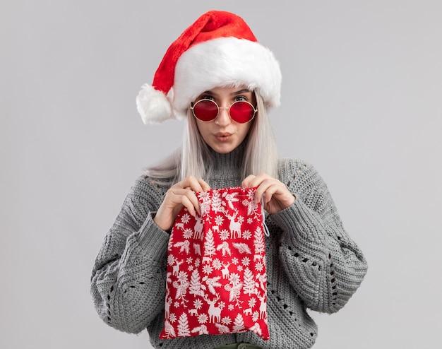 Jovem loira com um suéter de inverno e um chapéu de papai noel segurando uma bolsa vermelha de papai noel com presentes de natal, parecendo intrigada de pé sobre uma parede branca
