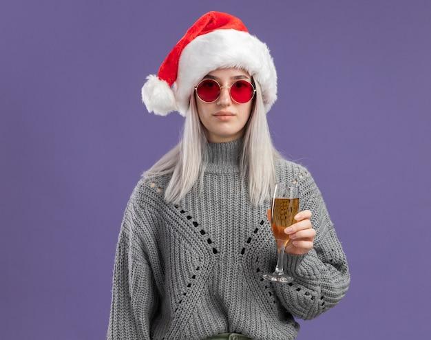 Jovem loira com um suéter de inverno e um chapéu de papai noel segurando uma taça de champanhe com uma expressão confiante em pé sobre a parede roxa