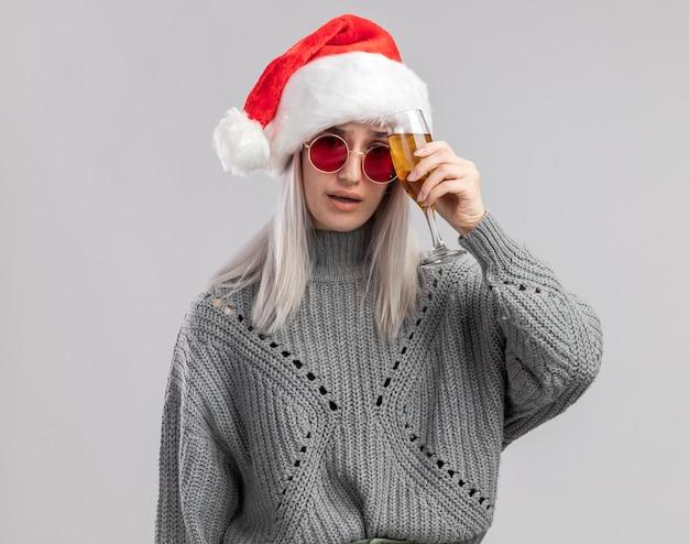 Jovem loira com um suéter de inverno e um chapéu de papai noel segurando uma taça de champanhe, parecendo indisposta e com dor de cabeça