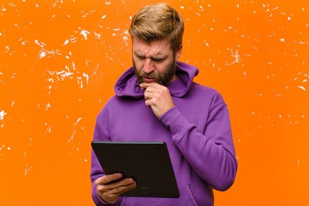 Jovem loira com um tablet usando um capuz roxo contra parede laranja danificada