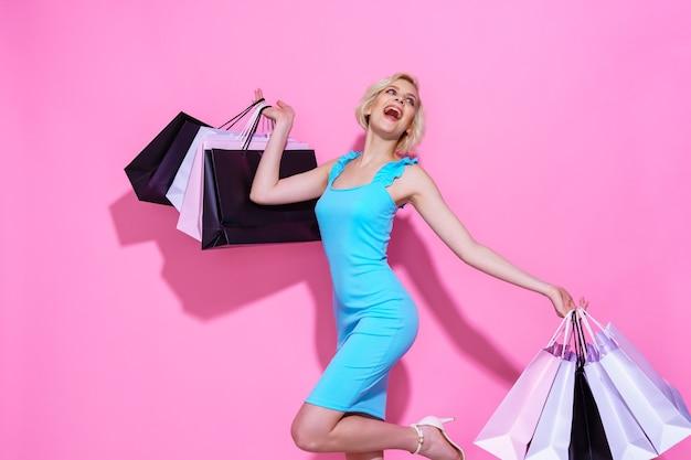 Jovem loira com um vestido azul segurando sacolas de compras em um fundo rosa