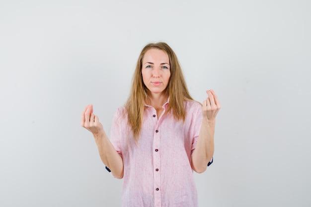 Jovem loira com uma camisa rosa casual