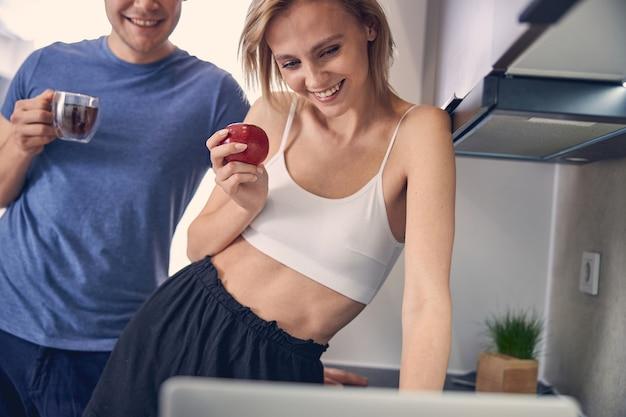 Jovem loira com uma maçã na mão navegando no computador enquanto o homem ao lado dela bebendo chá