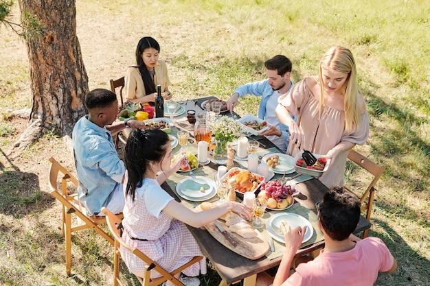 Jovem loira com vestido casual tirando alguns vegetais cozidos da tigela enquanto estava à mesa servida durante o jantar com os amigos