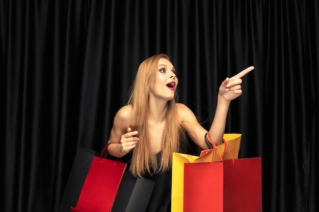 Jovem loira com vestido comprando na parede preta