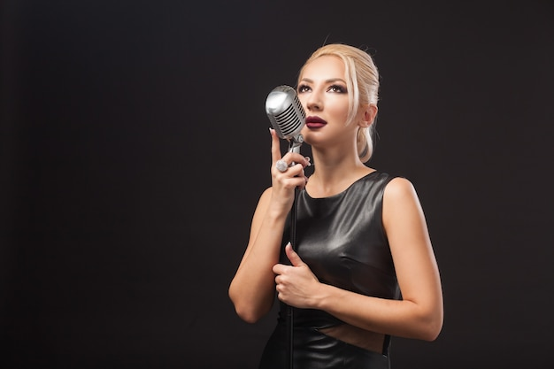 Jovem loira com vestido de couro preto segurando um microfone de metal nas mãos