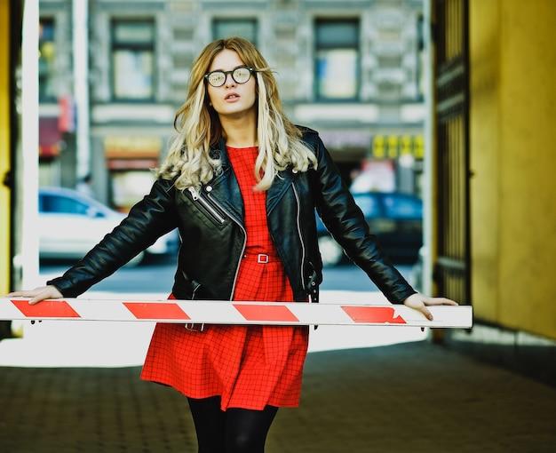 Jovem loira com vestido vermelho posando na cidade