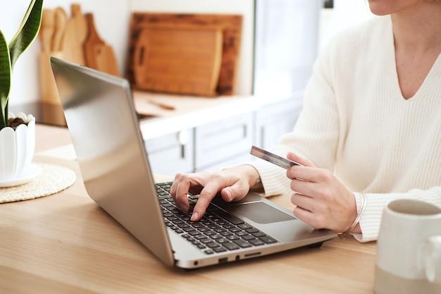 Jovem loira compra online com cartão de crédito no laptop, fazendo compras em casa