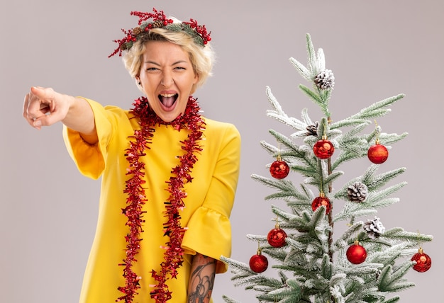 Jovem loira confiante com coroa de flores de natal e guirlanda de ouropel em volta do pescoço, em pé perto de uma árvore de natal decorada, olhando apontando em linha reta gritando isolado na parede branca
