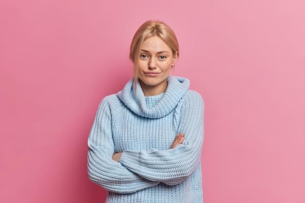 Jovem loira confiante séria e adorável mulher europeia escuta o interlocutor com expressão insatisfeita