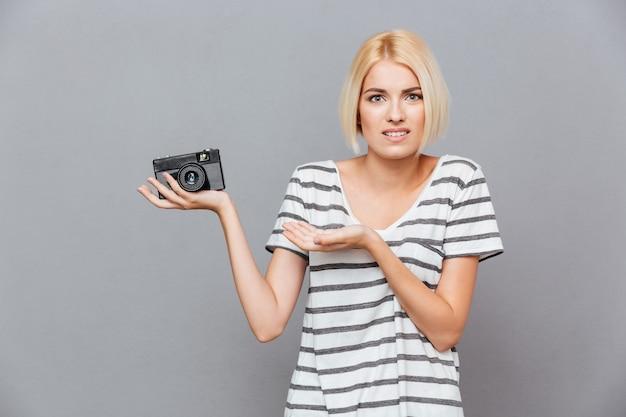 Jovem loira confusa segurando uma foto vintage antiga em frente à parede cinza