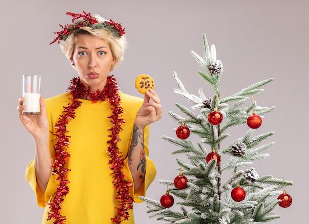 Jovem loira confusa usando coroa de flores de natal e guirlanda de ouropel em volta do pescoço, em pé perto de uma árvore de natal decorada, segurando um copo de leite e biscoito, parecendo isolado na parede branca