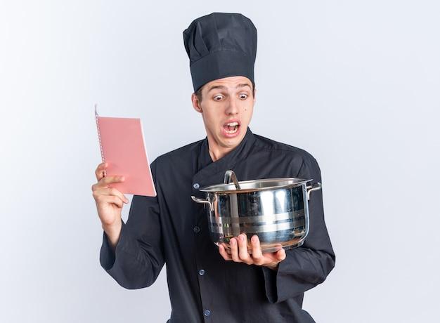 Jovem loira cozinheira assustada com uniforme de chef e boné segurando o bloco de notas e a panela, olhando para dentro da panela isolada na parede branca
