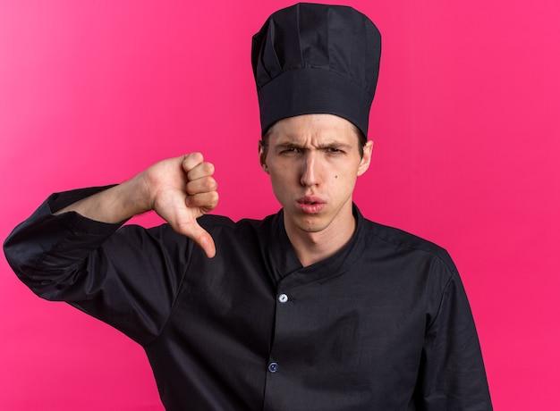 Jovem loira cozinheira carrancuda com uniforme de chef e boné, olhando para a câmera, mostrando o polegar para baixo isolado na parede rosa