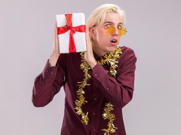 Jovem loira curiosa de óculos com guirlanda de ouropel em volta do pescoço, segurando um pacote de presente perto da cabeça, olhando para a câmera, isolada no fundo branco