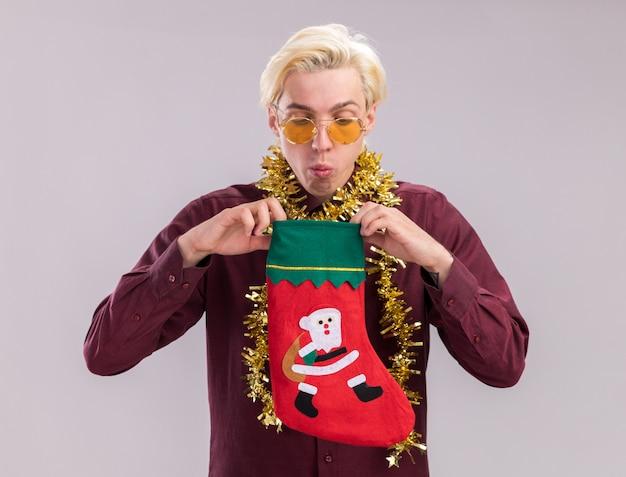Jovem loira curiosa de óculos com guirlanda de ouropel no pescoço, segurando uma meia de natal, olhando dentro, isolada no fundo branco