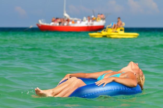 Jovem loira de biquíni azul andando no círculo de natação no mar e sorrindo num dia ensolarado de verão