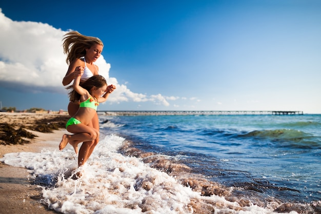 Jovem loira de biquíni branco e uma pequena garota feliz entrando no mar e se divertindo