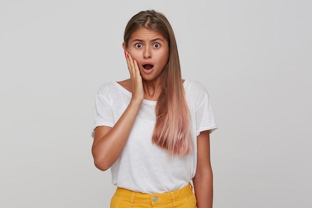 Jovem loira de cabelos compridos chocada com penteado casual, mantendo as mãos no rosto enquanto olha com olhos arregalados e boca aberta, isolada sobre uma parede branca