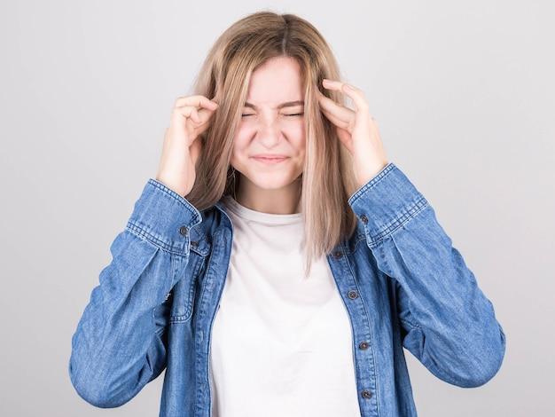 Jovem loira de camiseta branca e camisa jeans em um fundo cinza isolado, sofrendo de dor de cabeça