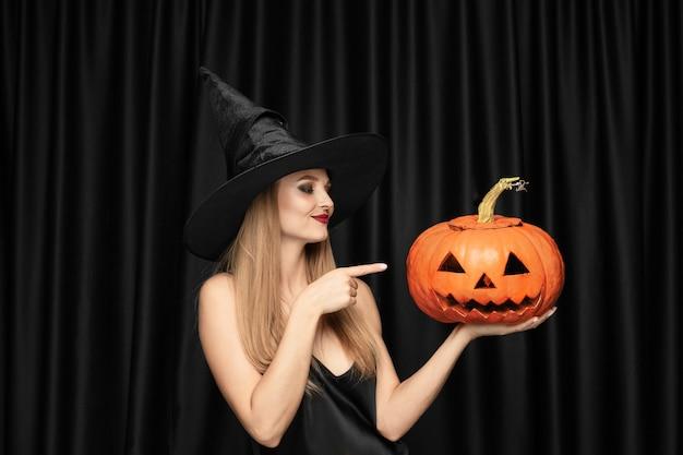 Jovem loira de chapéu preto e fantasia em fundo preto. modelo feminino atraente e sensual. halloween, black friday, cyber segunda-feira, promoções, outono