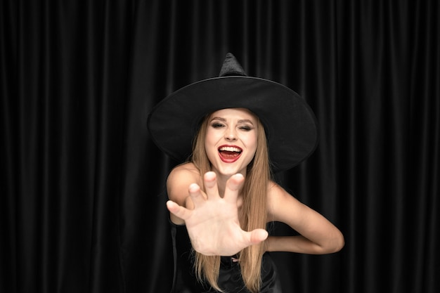 Jovem loira de chapéu preto e fantasia preta