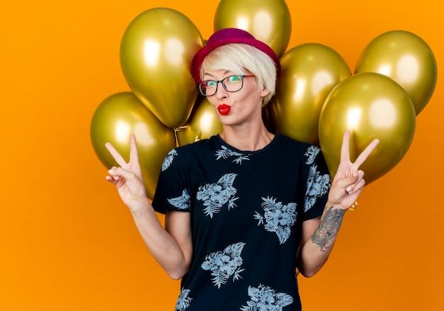 Jovem loira de festa impressionada com chapéu de festa e óculos em pé na frente de balões fazendo gesto de beijo e sinais de paz, olhando para frente isolada em parede laranja