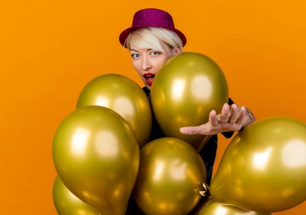 Jovem loira de festa impressionada com chapéu de festa em pé atrás de balões, olhando para a frente, estendendo a mão para a frente, isolada na parede laranja