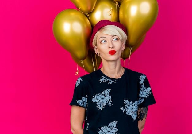 Jovem loira de festa impressionada com chapéu de festa em pé na frente de balões, olhando para o lado, mantendo as mãos atrás das costas isoladas na parede rosa com espaço de cópia
