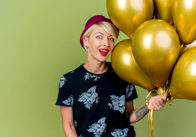Jovem loira de festa impressionada com chapéu de festa segurando balões olhando para frente, isolada na parede verde oliva com espaço de cópia