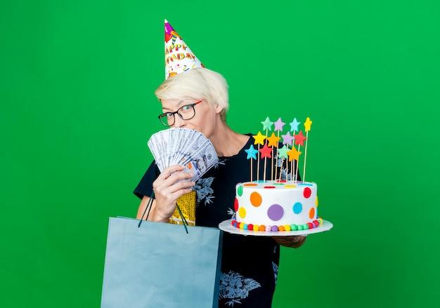 Jovem loira de festa impressionada com óculos e boné de aniversário segurando um bolo com estrelas, caixa de presente de dinheiro e saco de papel
