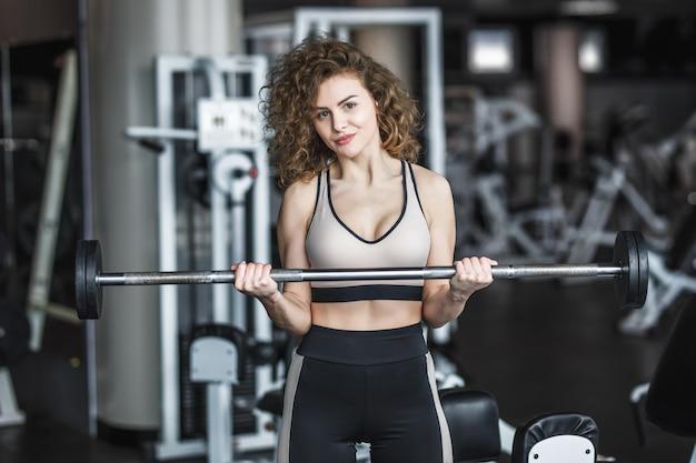 Jovem loira de instrutor de esportes vestindo roupas esportivas com halteres em uma academia, fazendo exercícios com uma barra
