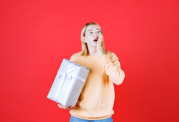 Jovem loira de jeans azul colocando a mão perto da boca enquanto segura a caixa de presente